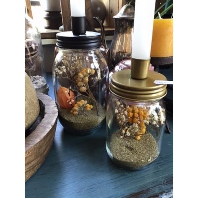 Pot met droog bloemen en kaarsenstandaard op deksel